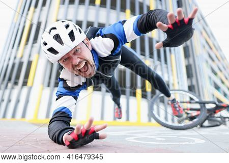 Young Male Cyclist Wearing Helmet And Protective Gear Fell Off Bike And Flying Portrait