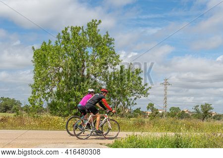 Campos, Spain; April 10 2021: Rural Road In The Interior Of The Island Of Mallorca With Two Cyclists