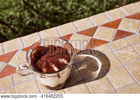 Traditional Italian Dessert Tiramisu In A Glass Cup On A Tile Table In The Garden. National Cuisine