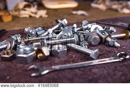 Metal Nuts Bolts And A Wrench Lie On The Work Table Of The Assembler In A Chaotic Order. Background