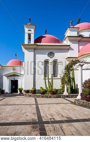 Place of worship and pilgrimage. The Monastery of the Holy Twelve Apostles. Israel. Capernaum. Snow-white church with pink domes. The concept of religious pilgrimage, educational and photo tourism