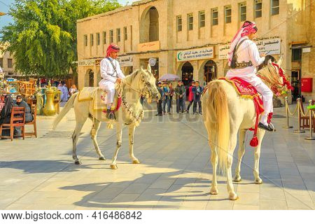 Doha, Qatar - February 20, 2019: Police On Horse In Traditional Clothes At Old Souq Waqif Riding Whi