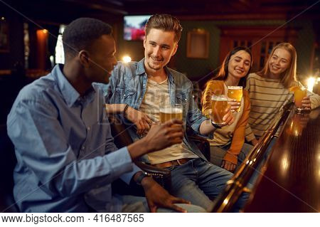 Four friends drinks beer at the counter in bar