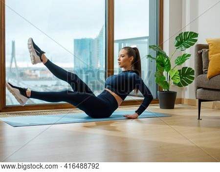 Young sportive woman with brown hair does abdominal exercises by panoramic window with street view and pot plant on balcony