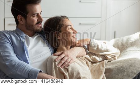 Happy Young Couple Relax At Home Dreaming Cuddling