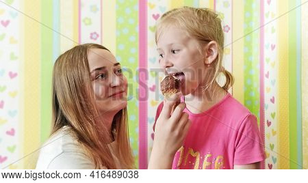 Older Sister Treats Younger Ice Cream. The Older Girl Gives The Younger One An Ice Cream To Try. Swe