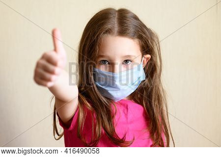 Kid In Face Mask For Protection To Corona Virus Shows Thumb Up, Portrait Of Pretty Little Girl Weari