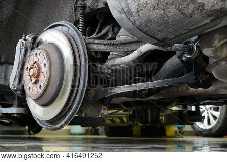 A Car On A Lift In A Car Service, A Wheel Was Removed From The Car. Suspension And Brake System Elem