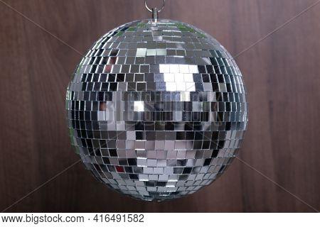 Shining Disco Ball dance music event equipment on wood background