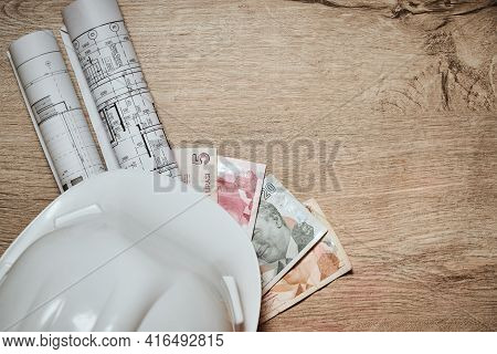 Rolled Engineering Drawings, White Hardhat And Turkish Lira At Wooden Table With Copy Space. Salary