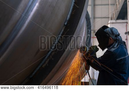 Production Of Large Diameter Pipes In The Factory Floor. Sparks From The Grinder. Bright Sparks From