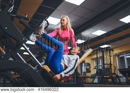 Personal Trainer Helping Woman In Works Out On Training Apparatus Inside In Fitness Center. Sporty L