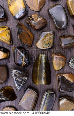 Tiger's Eye Rare Jewel On Brown Varnished Wood Texture. Sparse Mineral Pebbles Background.