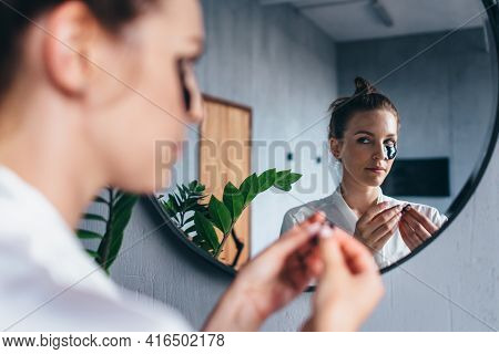 Young Woman Applies Patches Under Her Eyes