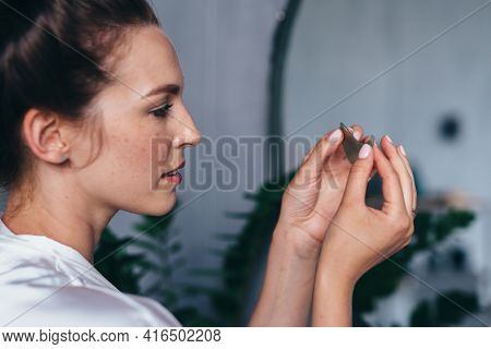 Young Woman Holds A Patch In Her Hand Before Applying It To Her Skin
