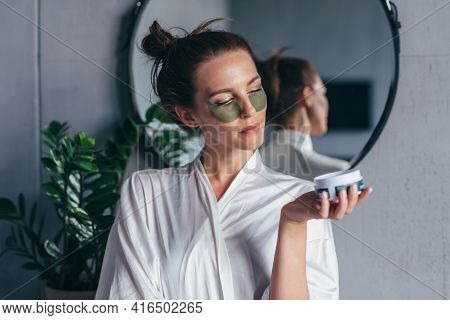 Woman Put Patches Under Her Eyes And Stands In The Bathroom