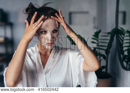 Young Woman Smoothing A Sheet Mask On Her Face