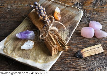 A Top View Image Of Several Pieces Of Holy Wood And Healing Crystals On A Hand Made Pottery Plate.