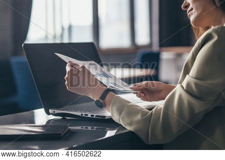 Woman At Her Desk Is Holding A Document And Looking At The Chart.