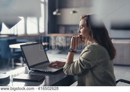Business Woman In A Suit Working With A Laptop At Her Desk In Her Home Office