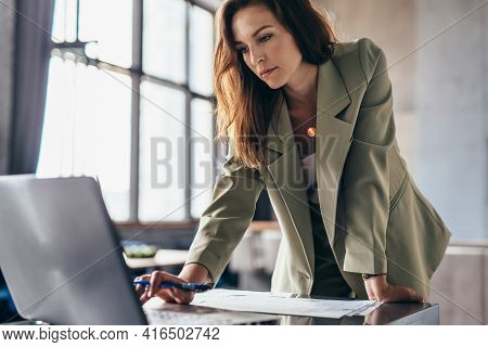 Woman Stands Leaning On Her Desk And Uses Her Laptop