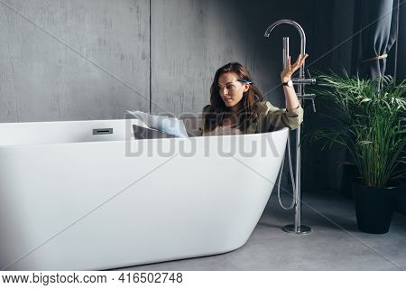 Woman Secluded In The Bathroom To Work And Sits In The Bath With Papers