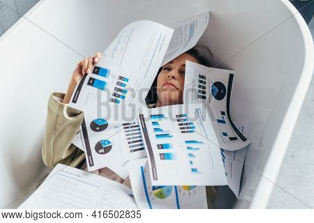 Woman Is Swamped With Work, With A Lot Of Paper, Documents Piled On Top Of Her. She Is Lying In The