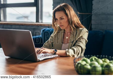 Woman At Home Sitting At Desk With Laptop