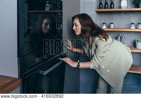 Woman Peeks Into The Oven To Check On A Baked Dish