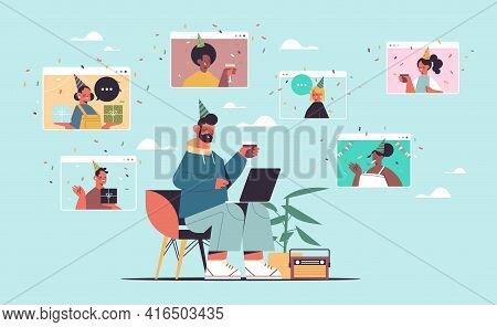 Man In Festive Hat Using Laptop Celebrating Online Birthday Party With Mix Race Friends In Computer
