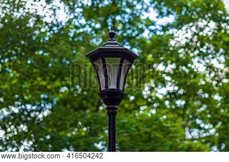 Streetlight In City Park Against Green Trees, Modern Energy-efficient Lamp In Retro Style