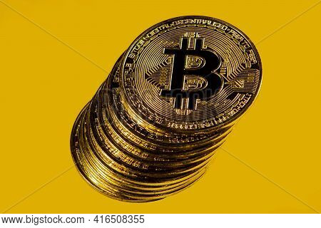 Close-up Of Gold Bitcoin Coins On Yellow Background.
