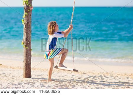Child On Swing. Kid Swinging On Tropical Beach. Travel With Young Children. Summer Family Vacation O