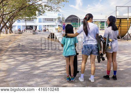 Two Little Girl Hand Hold Skateboard, Surf Skate On Public Skate Ramp Park Background. Free Relax Sk