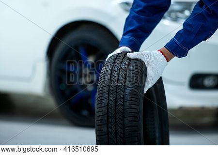 Close Up Of Car Mechanic's Hand Holds A Tire, New Tires That Change Tires In The Auto Repair Service