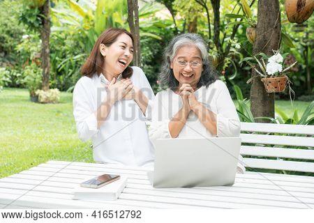 Asian Daughter Teaching Old Elderly Woman Use Online Social Media In Computer Laptop After Retiremen