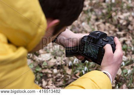 Vinnytsia, Ukraine - April 3, 2021. A Man In A Yellow Jacket Photographs Snowdrops. Spring Photo Hun