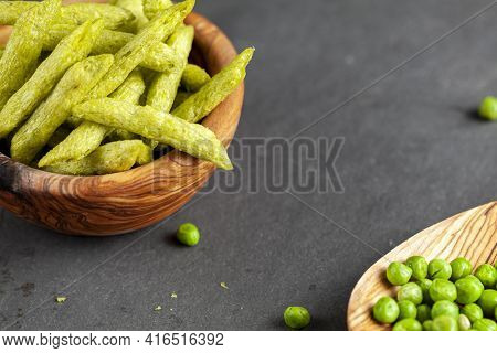 Closeup Isolated Image Of A Wooden Bowl Filled With Crunchy Harvest Green Snap Pea Snacks, A Healthi