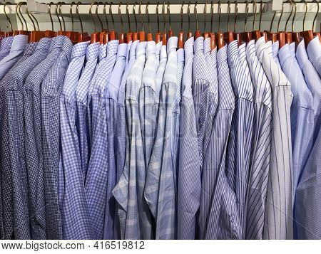 Row of Clothes hang on a shelf . Cloth Hangers with Shirts. ,striped shirts Men's business clothes. Fashion