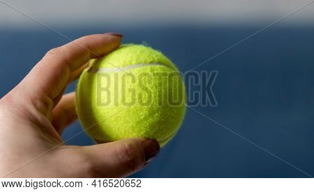 A Woman's Hand Holds A Tennis Ball On A Blue Background. Ready To Throw. Close-up. Free Space