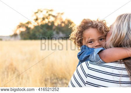 The face of an adorable curly haired African American boy in the arms of his mother in the outdoor sunlight. A happy and content expression as the mom shows love and affection to her son
