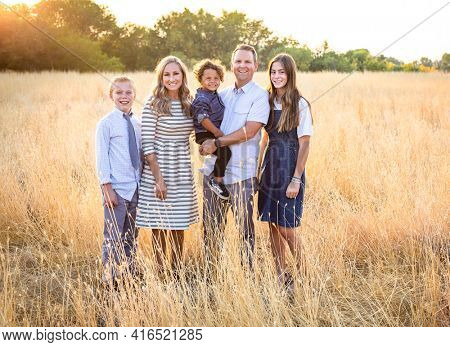 An elegant and beautiful young family portrait outdoors in a grassy field. Smiling and happy diverse group with a mixed race adopted baby boy and two other children