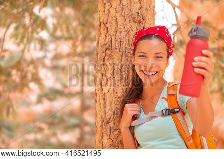 Water bottle to bring on hike for heat dehydration hydration. Happy Asian hiker drinking to stay hydrated on summer trail walking outdoor. Woman camping with backpack