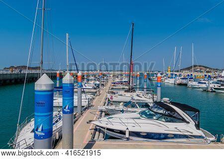 Pyeongtaek, South Korea; April 6, 2021: Yachts Moored At Jeongok Port Marina With Red Lighthouse In