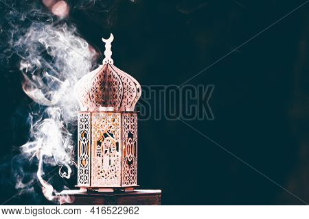 Ornamental Arabic lantern with with Holy Quran. Festive greeting card for Muslim holy month Ramadan Kareem.