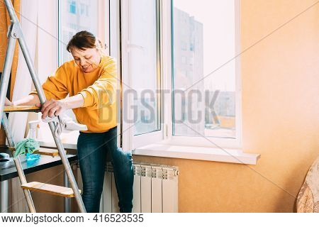Smiling Caucasian Woman Of Fifty In Yellow Sweater And Jeans Washes Dusty Window In Apartment. 50 Ye