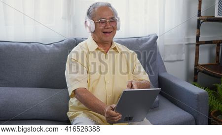 Old Man Grandfather Smile With Eyeglasses Relaxing Wear Headphones Is Listening To Music Using A Dig
