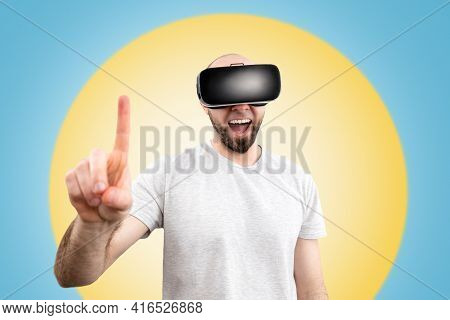 Vr Glasses. A Wondered Man In Virtual Reality Glasses, With His Mouth Slightly Open, Points A Finger