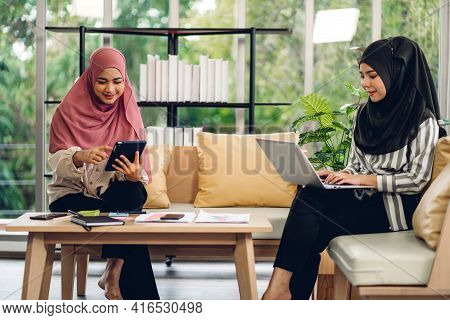 Young Two Smiling Happy Beautiful Asian Muslim Woman Relaxing Using Laptop Computer Working And Vide
