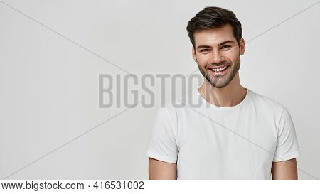 Real Emotions. Happy Bearded Man In White T-shirt Looking At Camera While Standing Against Grey Back